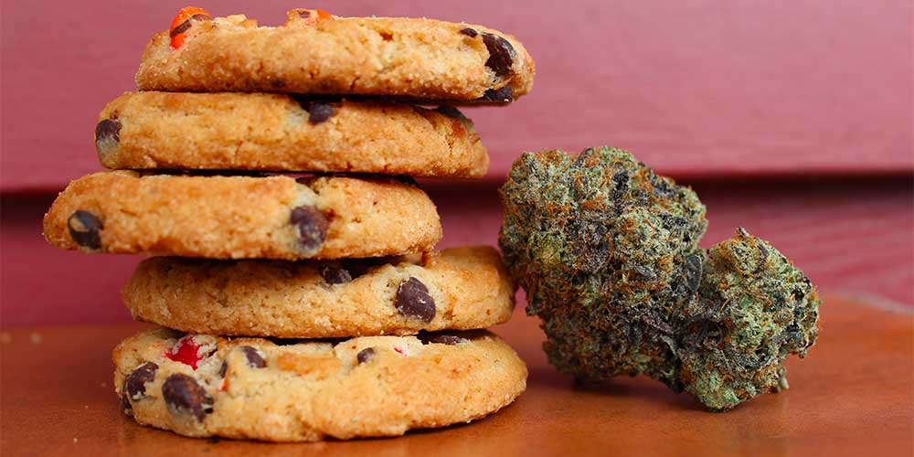 A stack of cookies sit next to a cannabis bud