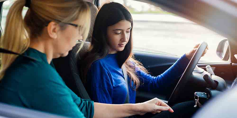 A young woman sits in the driver's seat next to an older woman