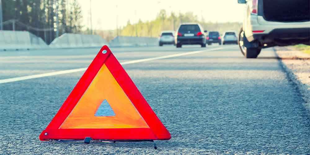 A hazard cone is shown on the side of a highway