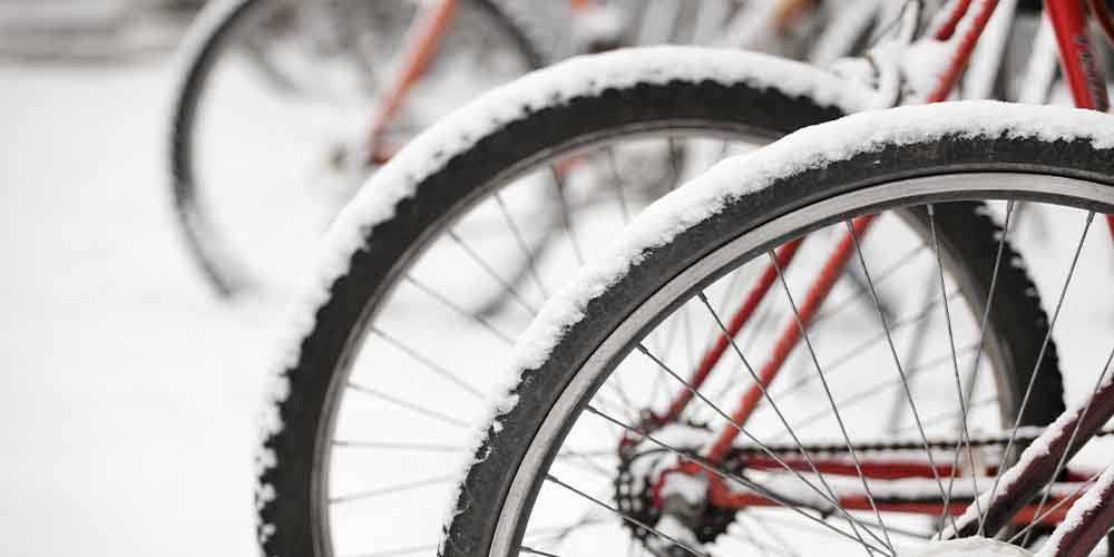 A row of bike tires covered in snow is shown