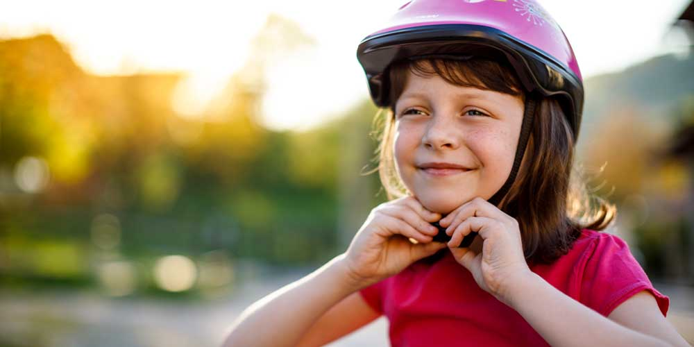 A young girl fastens the strap of her bike helmet