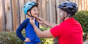 A father adjusts the strap of his son's bike helmet