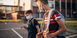 Two boys walk to school with face masks on