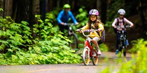 Kids ride their bikes on a path outdoors