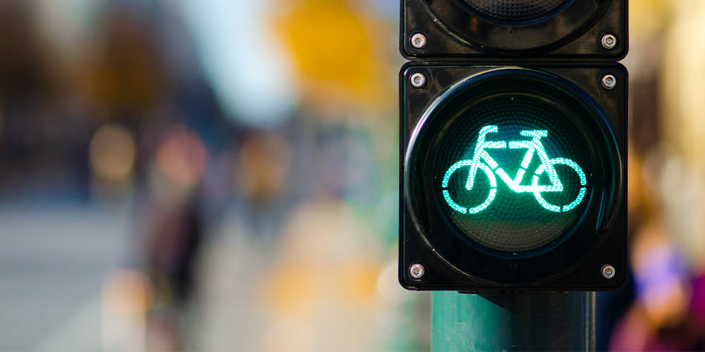 A traffic signal shows a green light shaped like a bicycle