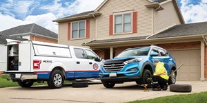 A CAA Roadside Assistance truck is shown in the driveway of a home, where a CAA mechanic changes the tire of a blue SUV