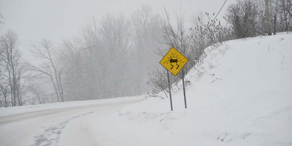 A snowy rural road is shown with a yellow caution sign that shows a car skidding