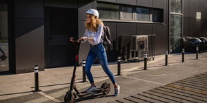 A woman rides her e-scooter on a city pathway
