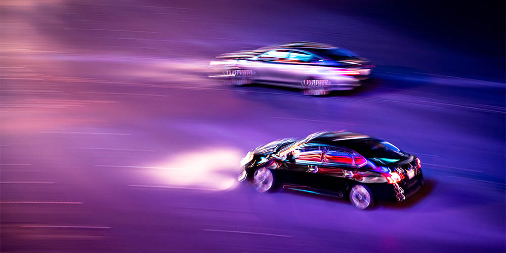 Two cars are shown racing at night on a purple background