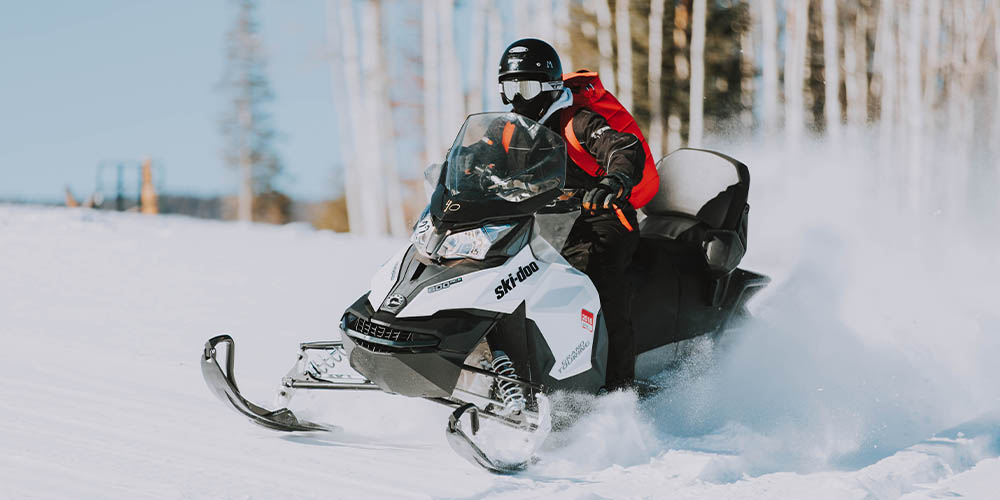 A person rides a snowmobile with trees in the background in the winter