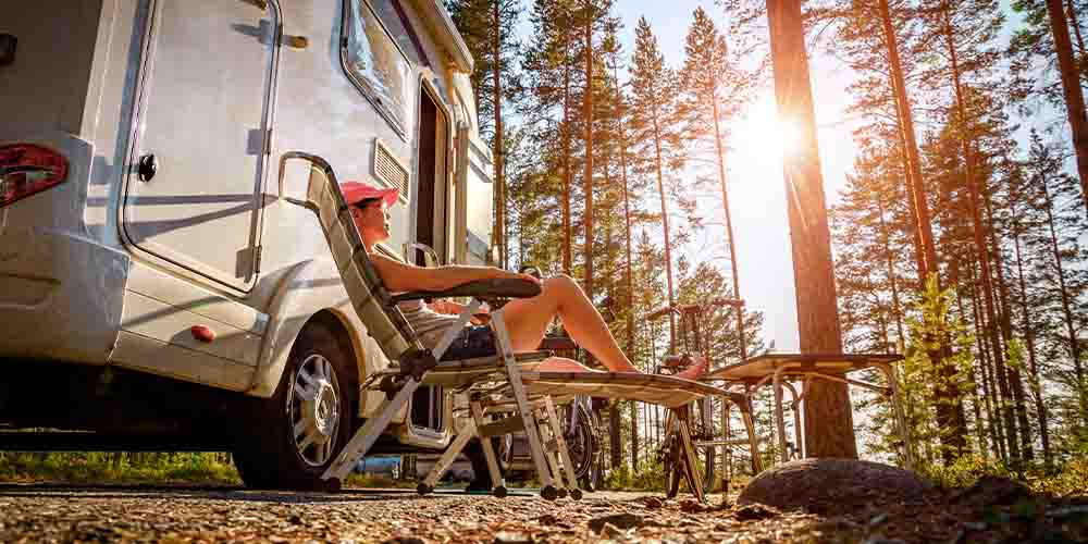A woman sits on a lawn chair next to an RV in the woods