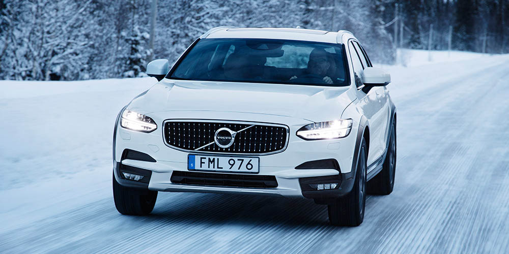 White Volvo V90 Cross Country driving on a snowy winter road