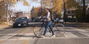 A woman and her child are shown crossing the road in a city on a sunny day