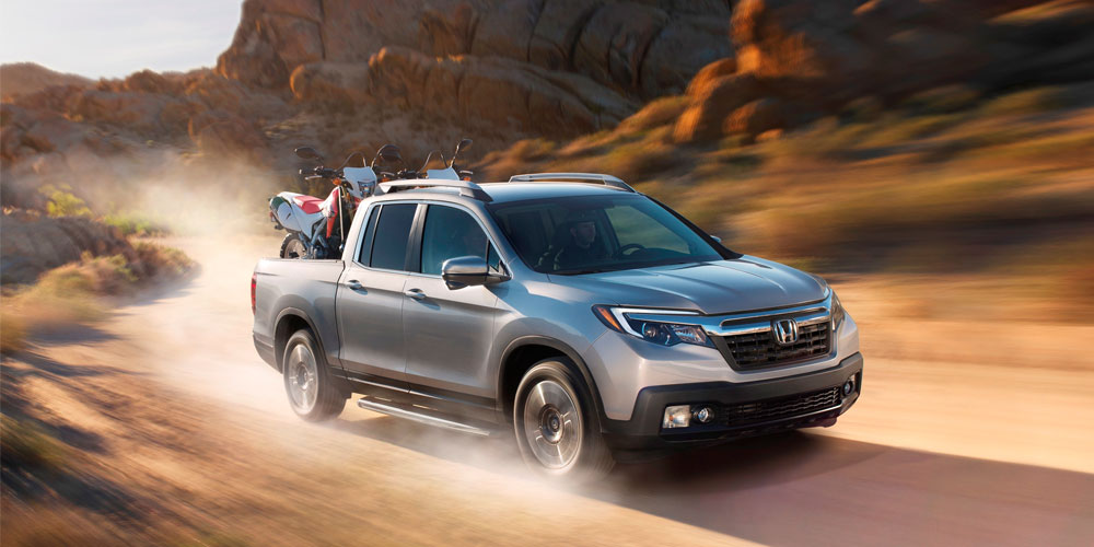 A grey 2017 Honda Ridgeline with motorbikes in the back driving through the desert and leaving dust behind