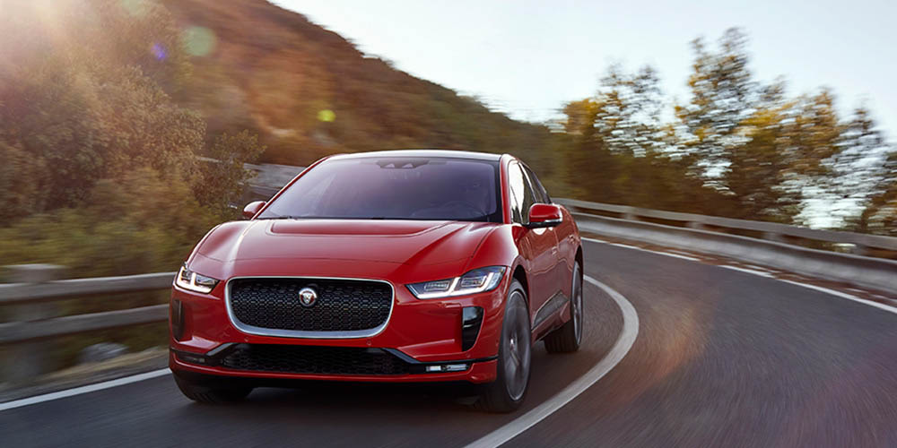 A red 2019 Jaguar I-Pace drives along the curve of a mountain