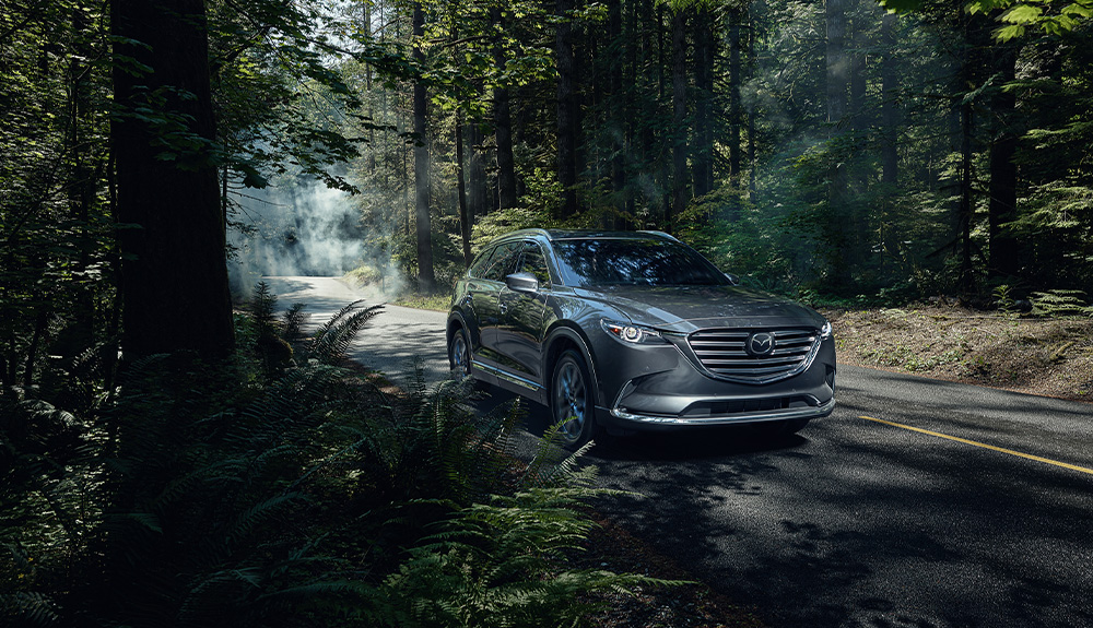 A grey Mazda CX-9 drives on a road through a forest.