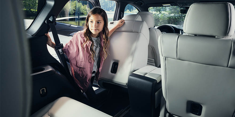 A young girls folds a second row seat forward to climb into the third row of the Mazda CX-9.