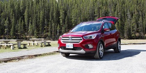 Red 2017 Ford Escape compact SUV with the trunk up outside with mountains in the background