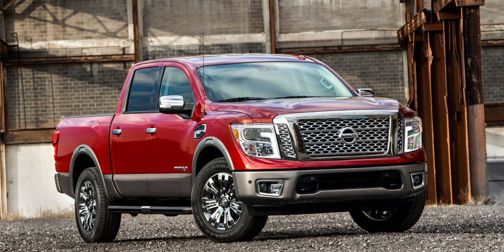 Red 2016 Nissan Titan XD Platinum Reserve parked in an industrial setting
