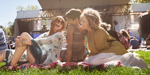 Three woman laugh together while sitting on blankets in the grass at an outdoor concert in Calgary, Alberta
