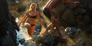 A man and woman in swimsuits explore the rocky shores in Tofino, British Columbia