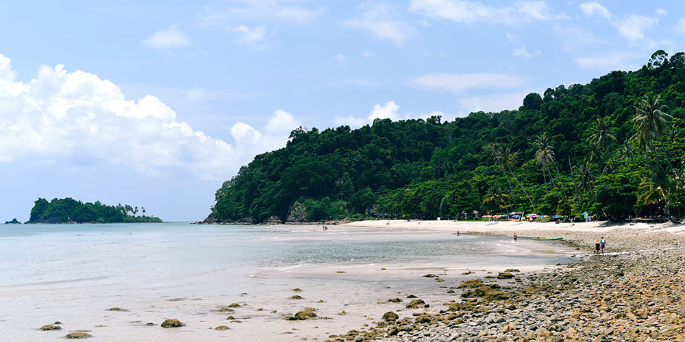 White sand beach with lush forest around it in Southeast Asia