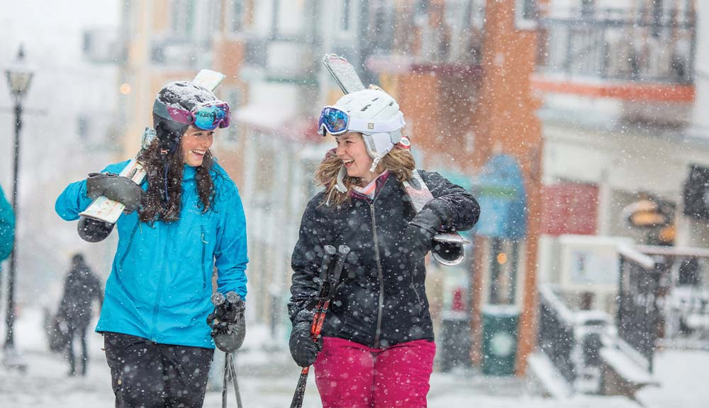 Two women carrying skis past shops in resort village at Mont Tremblant in Quebec Canada