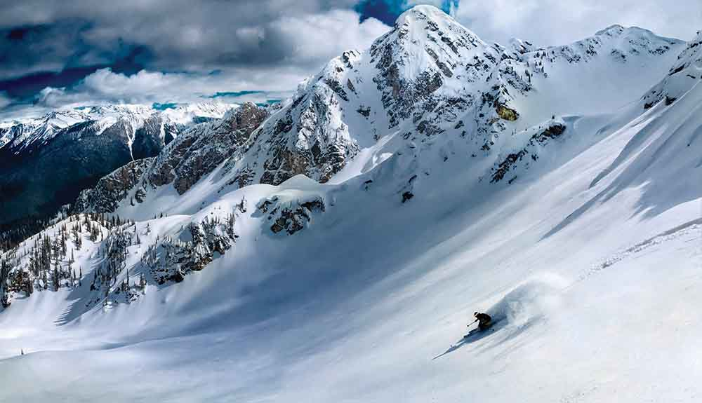 Single person skiing down the face of Revelstoke Mountain in British Columbia Canada