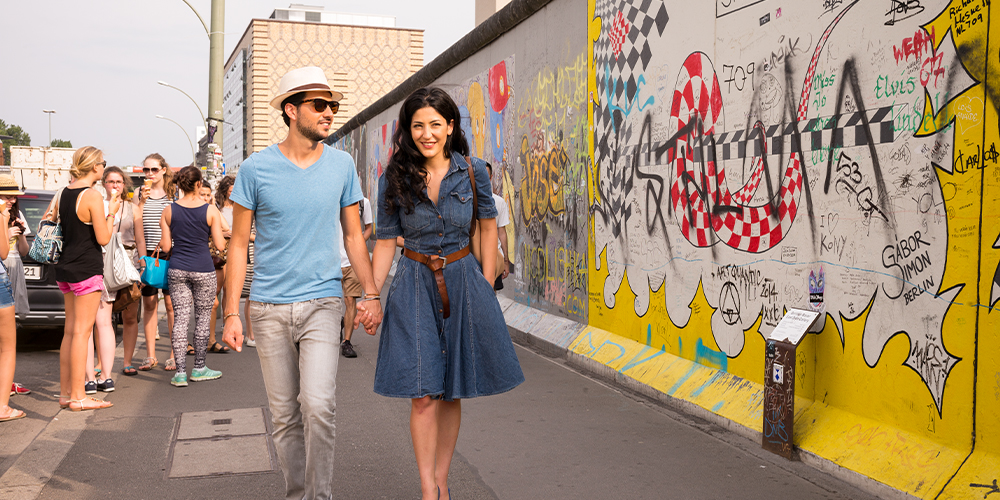 A couple walks along a wall painted with murals