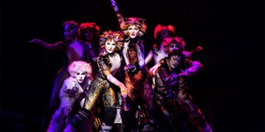 A group of cast members from the musical CATS on stage lit by red and purple lighting