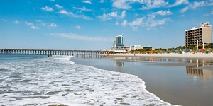 Sunny day on shore of Myrtle Beach with pier in the distance