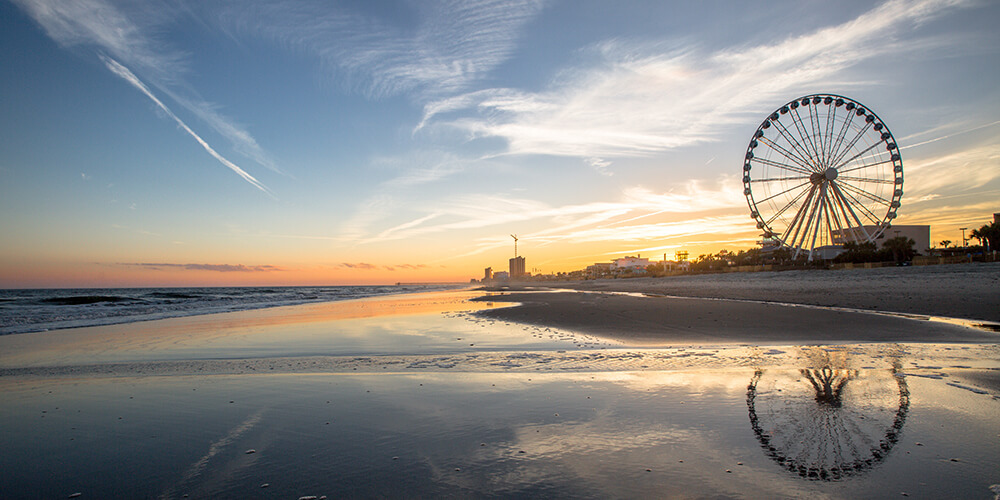 Myrtle Beach with Ferris wheel at sunset seen from shallow water