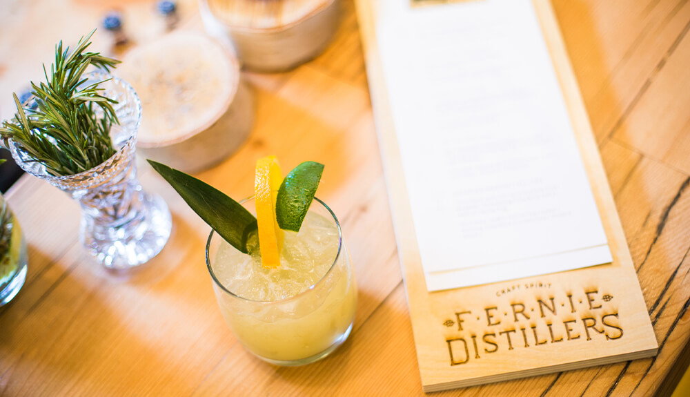 Drink menu and cocktail garnished with lemon slice on table at Fernie Distillers in Fernie, B.C., Canada