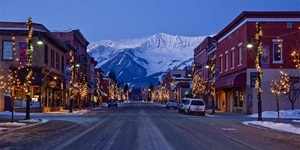 Looking toward red brick buildings, trees strung with lights and snowy mountains in the distance on Main Street in Fernie, B.C., Canada