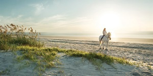 A woman rides a horse on the beach in Georgia's Golden Isles