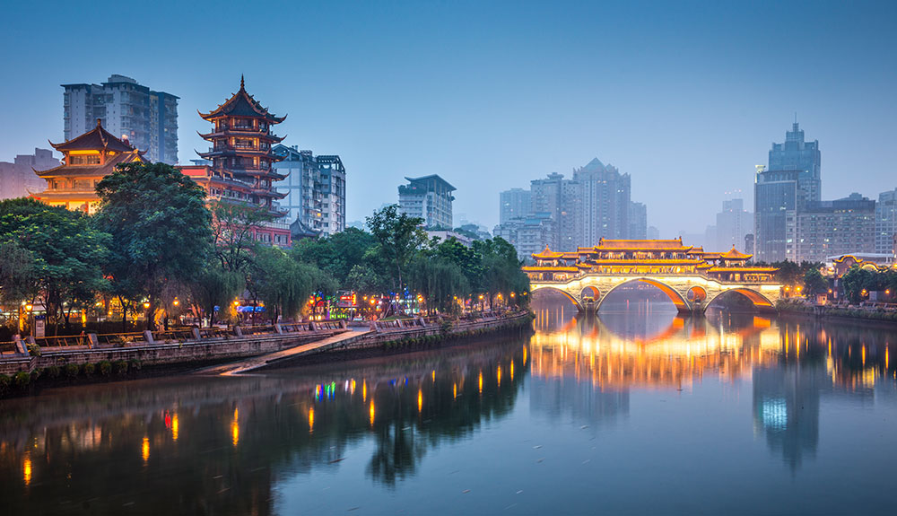 Pagodas behind trees along the coast as a bridge lit by pretty lights illuminates the water beneat it in Chengdu, China