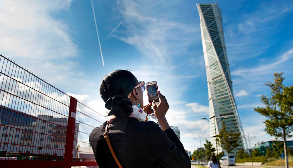 Woman wearing pink framed sunglasses capturing a photograph of Santiago Calatrava's Turning Torso in Malmo, Sweden
