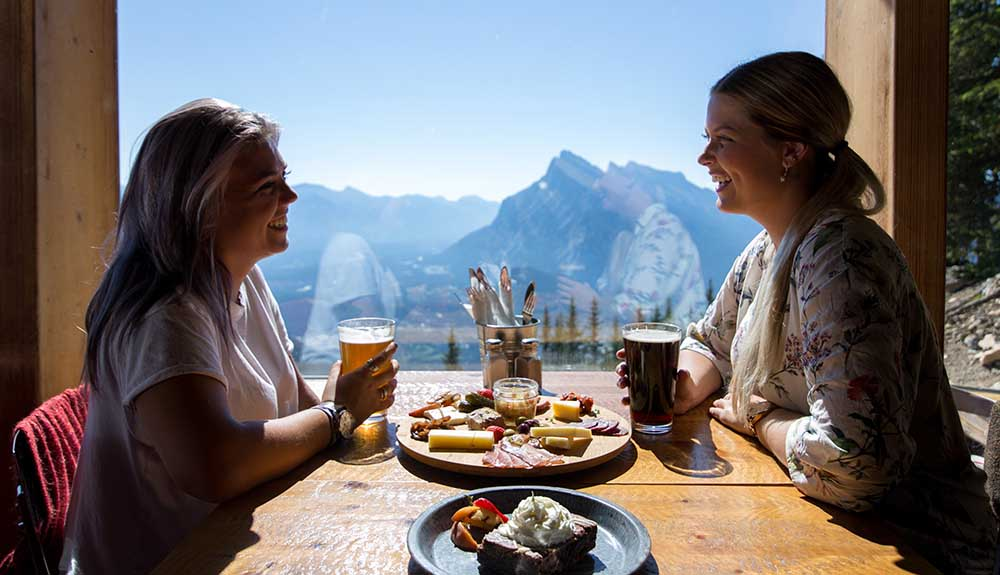 Two women dine at Cliffhouse Bistro at a table that looks out at the mountains.
