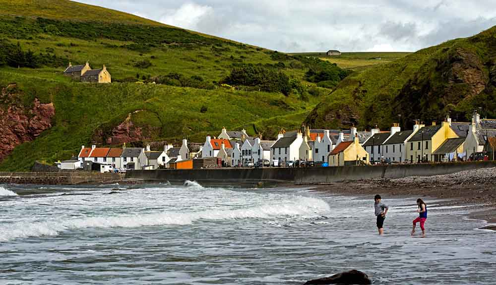 A few dozen fishing cottages line the shore in the village of Pennan, Scotland