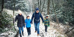 A family walks along a nature trail in the winter