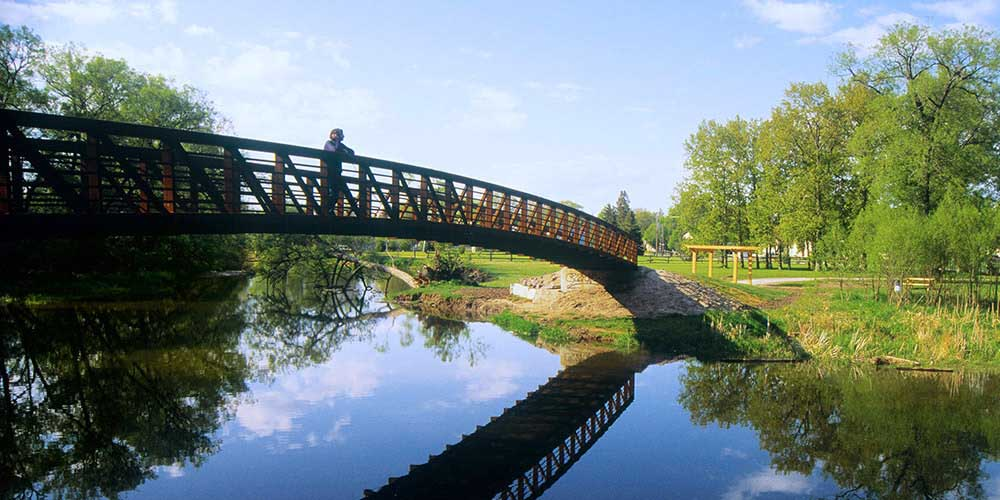 A pedestrian admires the view from a footbridge in the Kawarthas Northumerland region of Ontario.