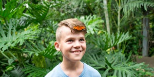 A boy with a butterfly on his head.