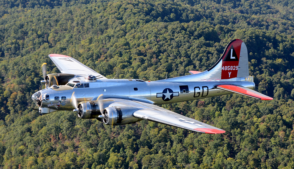 A vintage plane from the Yankee Air Museum flies over the tree line in Ann Arbor, Michigan.