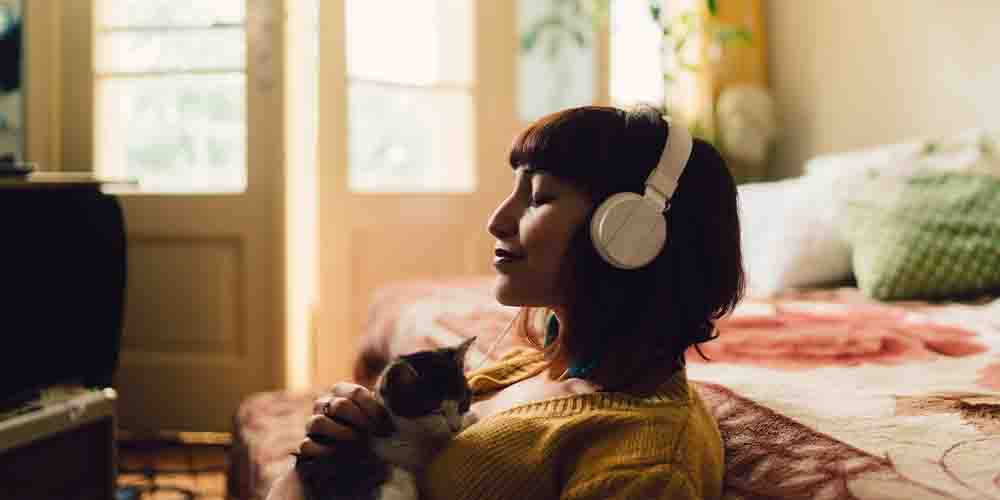 A young woman with headphones listening to music.