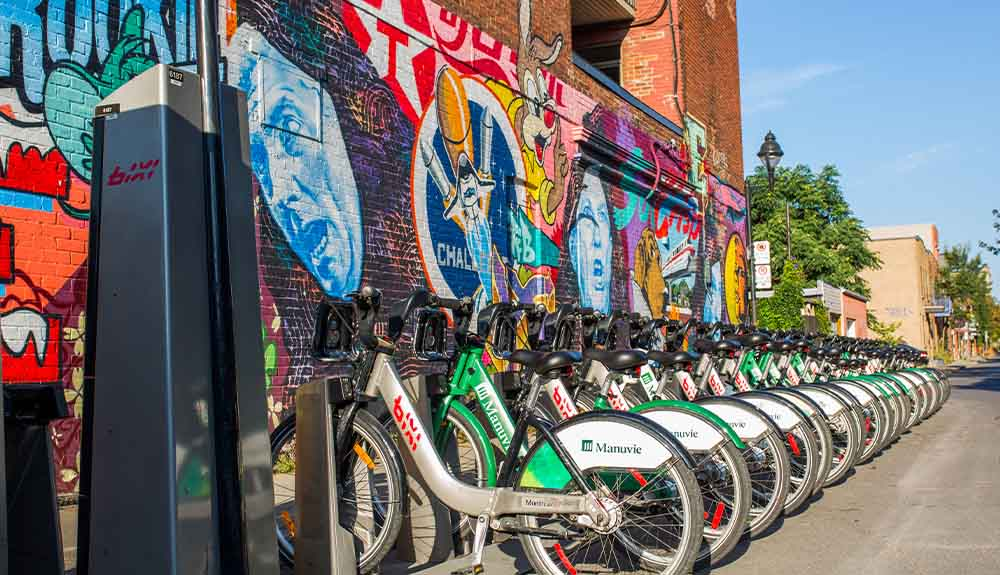 A row of Bixi bikes are secured on a side street in Montreal, Quebec