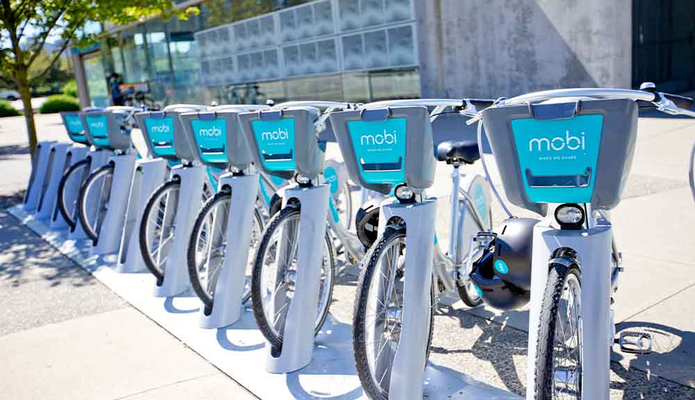 A row of Mobi bikes are parked on a street in Vancouver, British Columbia