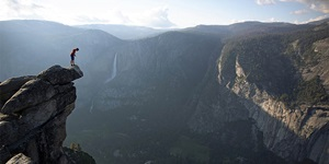 A hiker stands on the edge of a precipice over a mountain range