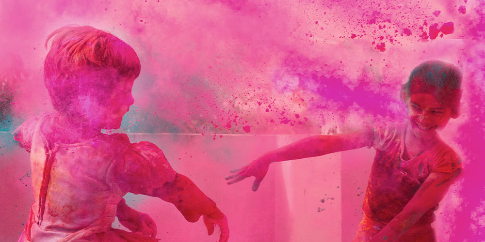 Two children are shown throwing bright purple powder at each other during Holi