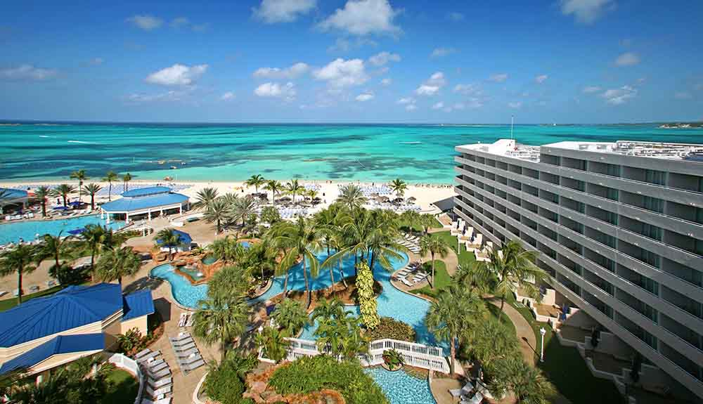 Aerial view of of the Melia Nassau Beach resort featuring the ocean and water pools