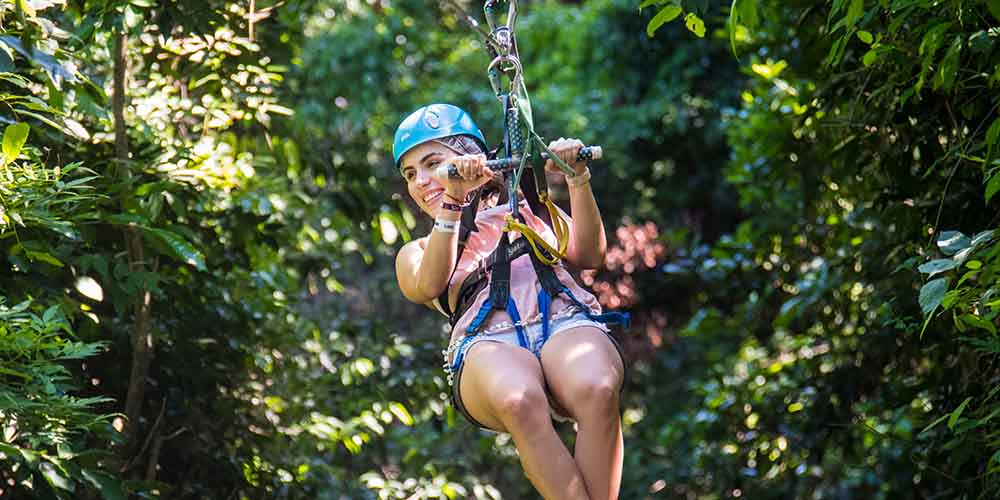 Woman wearing blue hat zip lining through a tropical forest